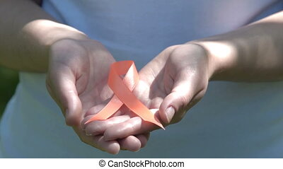 Woman holding orange awareness ribbon in hands - Close-up...