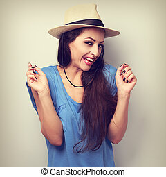 Happy giggling young woman with straw hat looking in camera...