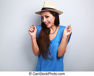 Happy giggling young woman with straw hat on blue background...