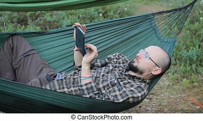 A man in a hammock touch tablet. Man in the woods with a...