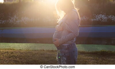 Pregnant woman in the summer nature meadow with in sunset -...
