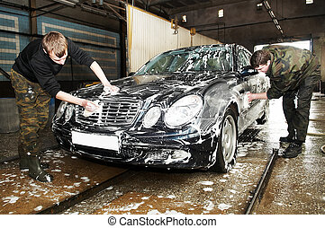 manual car washing cleaning with foam and water at service...