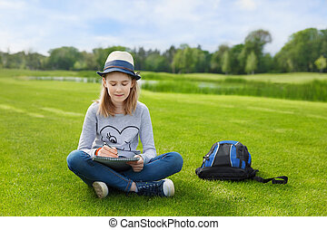 Lovely teenager girl drawing in the park - Teenager girl use...