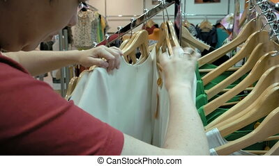 A female customer is browsing through the cloths. Video...