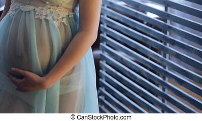 Pregnant woman in transparent clothes stands near wooden...