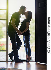 Mixed Race Pregnant Couple Kissing in Doorway. - Loving...