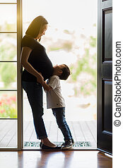 Young Son Hugging Pregnant Mom in Doorway - Loving Young Son...