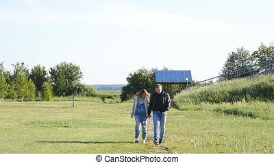 Pregnant woman with husband walking on meadow