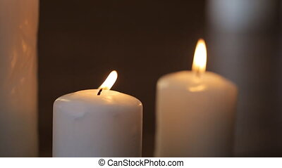 Pair of white wax candles shines brightly in dark room. They...