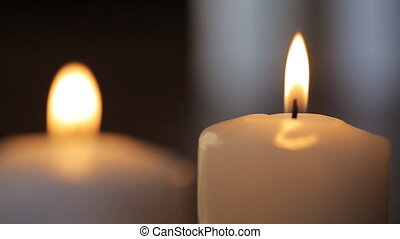 Two white candles burn in dark room to fill it with its...