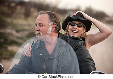 Mature couple riding a motorcycle in the desert