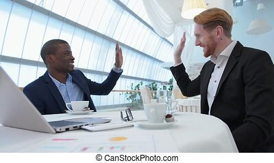 Business meeting in restaurant - Businessmen giving five to...