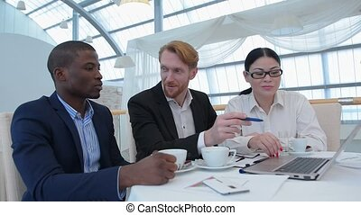 Business meeting in restaurant Businessman in centre...