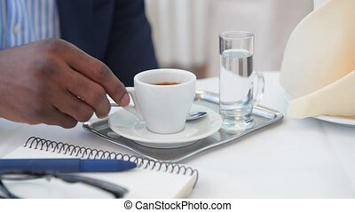 Businessman sitting in restaurant and drinking cup of coffee...