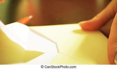 Girl sealing a romantic letter and putting it into a heart-shaped box