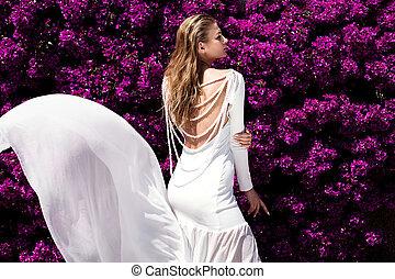 Elegant girl in white dress over flowers.