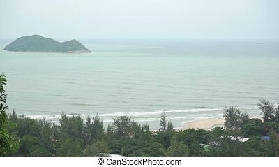 Tide and distant small island behind tropical forest Slow...