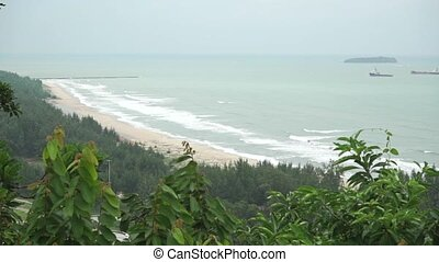 Surf, distant ships and small island behind tropical forest....