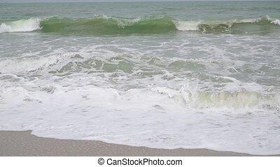 Slow motion video of foamy sea surf on sandy beach