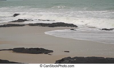 Sea surf on rocky and sandy beach. Slow motion video shot on...