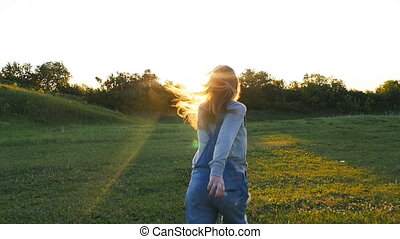 A pregnant woman is running on the grass at sunset