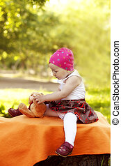 little girl enjoys playing with Teddy Bear in summer