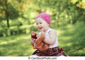 happy girl laughing and playing with Teddy bear in summer...