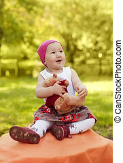 happy little girl in cap playing with Teddy bear in summer...