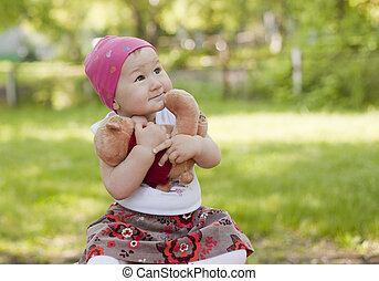 Little girl playing with a Teddy bear hugged him and not...