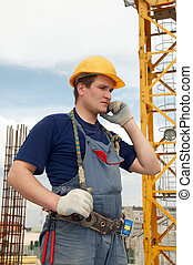 builder at construction site with phone - One worker builder...