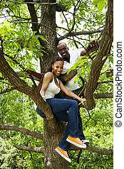 Happy fun African couple in tree