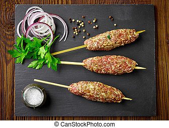raw minced meat skewers kebabs on wooden table