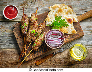 grilled minced meat skewers kebabs on wooden table