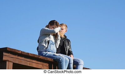 couple in love sitting on the roof at sunset