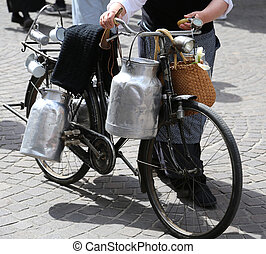 elderly woman with old bicycle and milk cans - elderly woman...