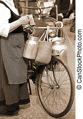 elderly woman carrying milk cans with a old bicycle - woman...