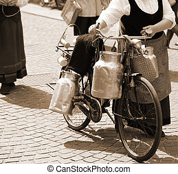 aluminium milk cans transported on old bike of the elderly...