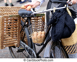 old woman on bike with two fresh eggs in hand