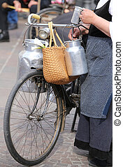old woman with very old bicycle and milk cans - elderly...