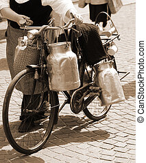 woman carrying milk cans with a old bicycle - elderly woman...