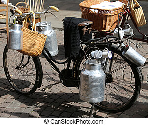 milk cans transported on old bike of the milkman - aluminium...