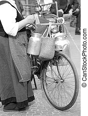 elderly woman with bicycle and aluminium milk cans - elderly...