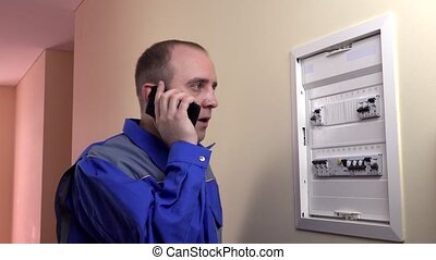 Man working on a circuit breaker and phoning Static shot
