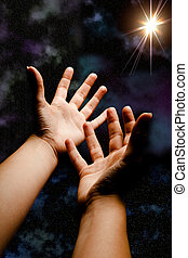 Reaching for the star - Hands in outer space reaching for a...