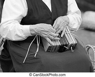 hands of an elderly woman while creating a bag - hands of an...