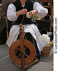 woman with wooden spinning wheel while spinning a yarn -...