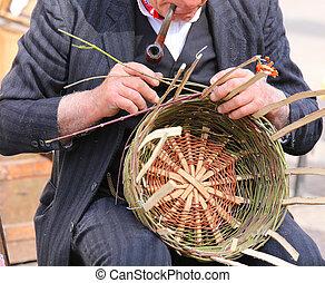 old man smoking his pipe creates a straw basket - man...