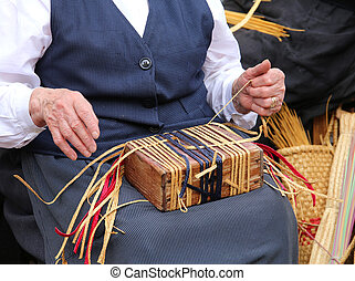 elderly woman while creating a straw bag - hands of an...