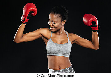 Portrait of a smiling fitness woman standing with boxing...