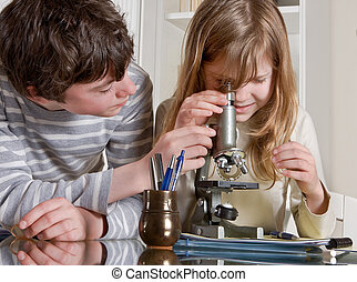 Science for kids - Two teenagers helping each other with a...